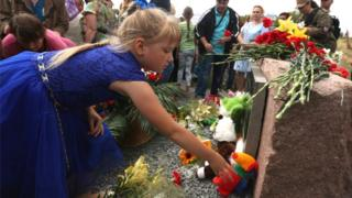 People lay flowers at the monument to the victims of the Malaysia Airlines flight MH17 crash, in the village of Grabovo, Ukraine, 17 July 2017