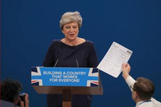 Comedian Simon Brodkin, also known as Lee Nelson confronts Prime Minister Theresa May during her speech at the Conservative Party Conference at the Manchester Central Convention Complex in Manchester.