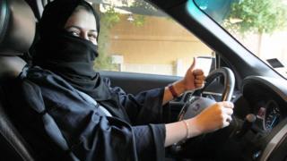 A woman gives a thumb up as she sits behind the wheel of a car in Riyadh, Saudi Arabia, 27 September 2017