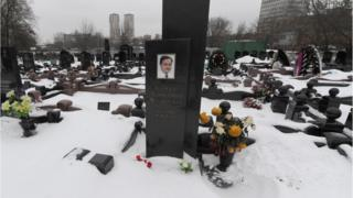 A picture taken on December 7, 2012, shows snow clad grave of Russian lawyer Sergei Magnitsky with his portrait on the tomb (C) in Moscow.
