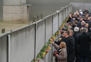 in_pictures People stick flowers into slats of a still-standing section of the Berlin Wall, following a ceremony to celebrate the 30th anniversary of the fall of the wall in 1989.