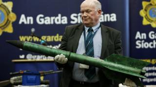 Detective Sergeant Tom Carey holds a rocket, one example of the weapons seized over the last two years by detectives combating dissident republic violence in the Republic of Ireland