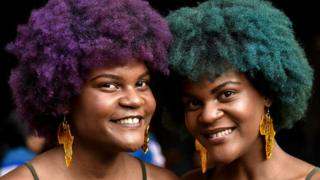 Two women with brightly coloured Afro hair