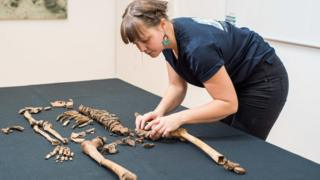 Team member Clara Alfsdotter arranges the remains of one victim of the Sandby Borg massacre