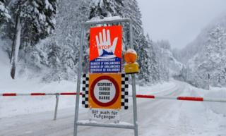 A sign warning of avalanche danger is seen on a closed road after heavy snowfall near Obertauern, Austria