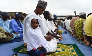 A girl and her father at Eid prayers in Ibafo, Ogun state, Nigeria - Tuesday 21 August 2018