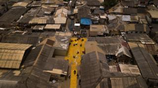 Aerial shot of yellow tapestry created by artist Serge Attukwei Clottey on roads in La - Accra, Ghana
