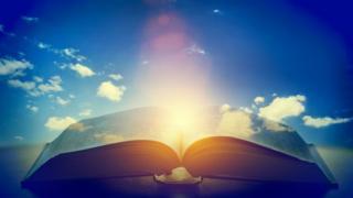 Libro abierto con una luz en el medio.