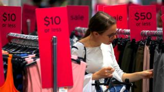 A woman browses sale racks at a Topshop store in Sydney