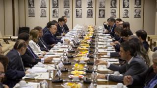 Meirelles comanda reunião ao lado de outras pessoas sentadas em mesa, e com fotos de ex-ministros ao fundo, em foto de 2016