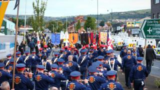 Orange Order lodges and bandsmen marching past the Ardoyne shops in north Belfast early on Saturday morning
