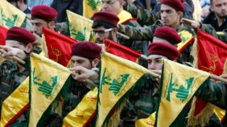 Members of Lebanon's Hezbollah movement hold up flags as they march during the funeral of a fighter in Kfour (1 March 2016)