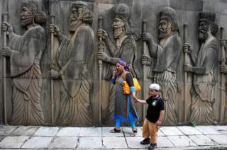 A Parsi devotee and child walk past a sculpture after offering prayers at a fire temple in Mumbai
