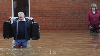 Residents carry possessions from their flooded homes in Carlisle