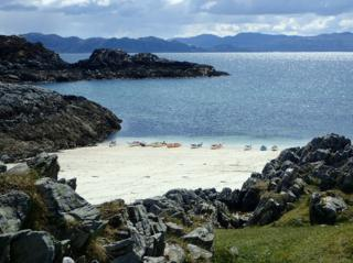Kayaks lined up on Arisaig beach.