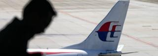 A file picture dated 17 July 2016 shows a passenger walking past a Malaysia Airlines aircraft within a viewing gallery of the Kuala Lumpur International Airport (KLIA) in Sepang, outside Kuala Lumpur, Malaysia