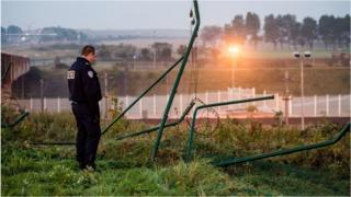 A policeman stands by a breached fence at the Eurotunnel terminal