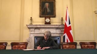 İngiltere Başbakanı Theresa May, Brexit sürecini başlatacak olan mektubu imzalarken.
