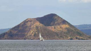 Tourists sail past the volcanic crater locally known as Binintiang Malaki (big extended leg), part of the Taal volcano islan
