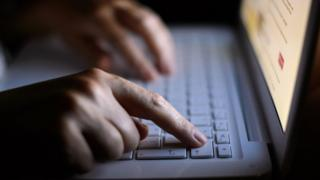 Photo of a man's hands on a laptop keyboard.