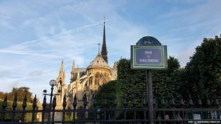 A street sign with Nina Simone's name in front of Notre Dame cathedral