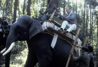 Prince Philip, Duke of Edinburgh rides an elephant during a visit to the Kanha game reserve on 21 November 1983 in in India.