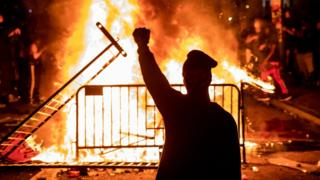 A protester stands in front of a flaming barricade holding a fist in the air.