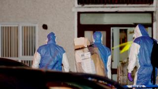 People in forensic suits arrive at the scene of the incident