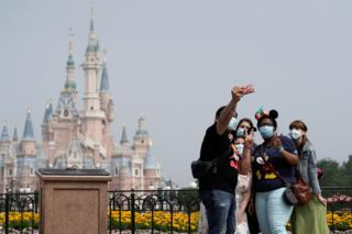 Visitors wearing protective face masks pose for a picture at Shanghai Disney Resort