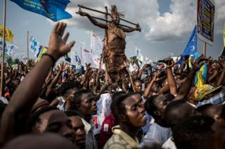 Supporters of Democratic Republic of Congo joint opposition presidential candidate Martin Fayulu sing and dance as they wait for him to address the crowd after his arrival in Kinshasa to launch his campaign on November 21, 2018. -