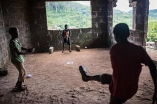 Boys play football with a plastic bottle in a back room of the house