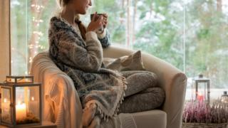 Stock image of woman wrapped up in knitwear with fairy lights and a hot drink