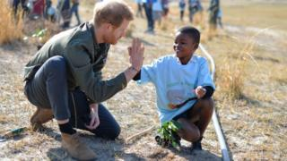 Prince Harry with a child planting trees