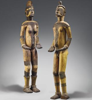 The wooden objects, one male and one female, represent deities from the Igbo community