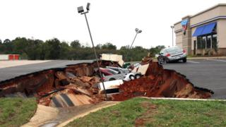 This photo shows vehicles after a cave-in of a restaurant parking lot in Meridian, Miss., Sunday, Nov. 8, 2015.