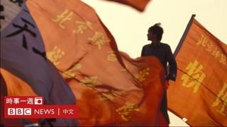 天安門廣場各集會單位旗幟下一名年青人站立著(1/6/1989)