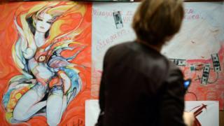 మాస్కోలోని ఆండ్రీ సఖరోవ్ మ్యూజియంలో 2013 డిసెంబర్ 17వ తేదీన సెక్స్ వర్కర్లు ప్రారంభించిన చిత్రకళా ప్రదర్శనను తిలకిస్తున్న ఒక మహిళ