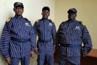 Three customs officers stand next to each other in their new, blue-and-white striped uniforms.