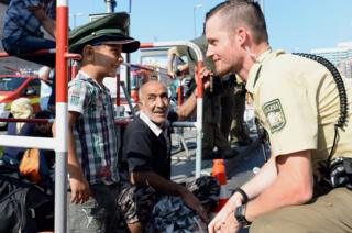 Refugee boy wearing German policeman's hat in Munich, 1 Sep 15