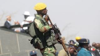 An armed member of the Zimbabwe National Army (ZNA) stands guard