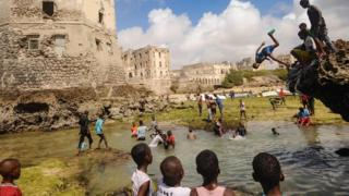 Somali children dive, play and swim in front of the ruins of an old building on the coastal district of Hamarweyne, in Mogadishu on Friday.