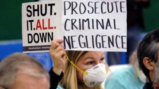 A Porter Ranch resident holds a protest sign against the gas leak near Los Angeles (16 January 2016)