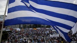 A protester waves a Greek flag during an anti-austerity pro-government rally in front of the parliament building in Athens, Greece, on 21 June 2015.