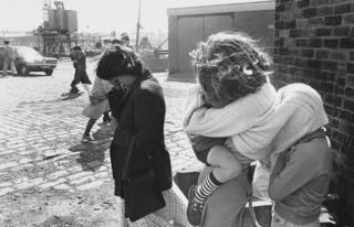 Woman cuddling child, 1963