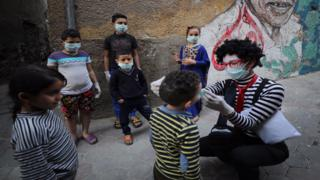 in_pictures Egyptian clown Ahmed Naser wearing a face mask helps children to put on face masks