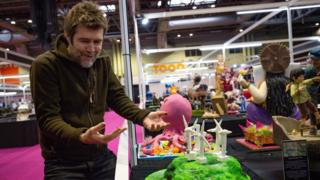 Comedian Rhod Gilbert delivering his creation during Cake International 2019 at the NEC, Birmingham