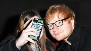 A fan takes a picture with Ed Sheeran