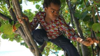 Yashua Mack playing in a seagrape tree