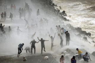 People gather by the Marine Drive seafront to be hit by breaking waves at high tide in Mumbai, India