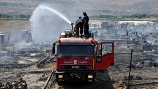 Firefighters put out fire at refugee camp in Lebanon on 2 July 2017